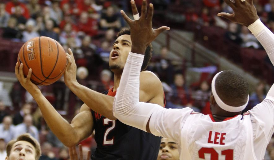 Maryland's Melo Trimble (2) shoots against Ohio State's Anthony Lee (31) during the first half of an NCAA college basketball game in Columbus, Ohio, Thursday, Jan. 29, 2015. (AP Photo/Paul Vernon)