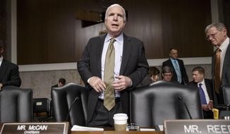 Senate Armed Services Committee Chairman Sen.John McCain, R-Ariz., stands up at the start of a hearing with former Secretary of State Henry A. Kissinger, Thursday, Jan. 29, 2015, on Capitol Hill in Washington. Protesters interrupted the start of a Senate Armed Services hearing as they shouted at Kissinger, calling him a war criminal. Sen. James Inhofe, R-Okla., is at right. (AP Photo/J. Scott Applewhite)