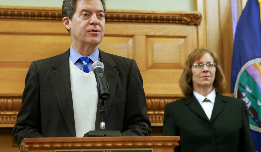 Kansas Gov. Sam Brownback, left, introduces Kathryn Gardner, right, as his nomination to fill an empty seat on the Kansas Court of Appeals on Thursday Jan. 29, 2015, at the Kansas Statehouse in Topeka, Kan. (AP Photo/The Topeka Capital-Journal, Chris Neal)