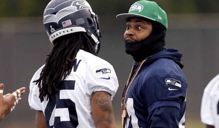 Seattle Seahawks' Marshawn Lynch, right, talks with Richard Sherman during a team practice for NFL Super Bowl XLIX football game, Thursday, Jan. 29, 2015, in Tempe, Ariz. The Seahawks play the New England Patriots in Super Bowl XLIX on Sunday, Feb. 1, 2015. (AP Photo/Matt York)