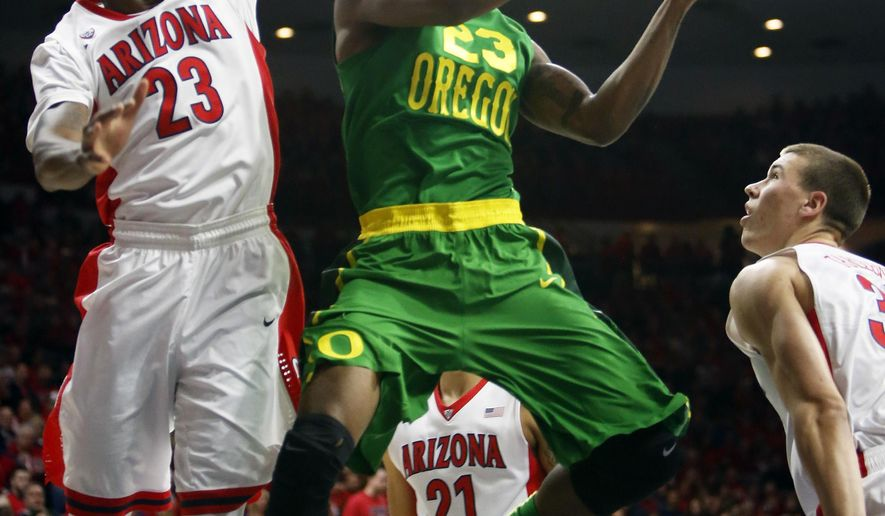 Oregon forward Elgin Cook, center, drives on Arizona forward Rondae Hollis-Jefferson during the first half of an NCAA college basketball game, Wednesday, Jan. 28, 2015, in Tucson, Ariz. (AP Photo/Rick Scuteri)