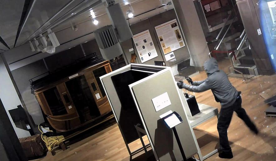 In this image from surveillance video released by the FBI,  a suspect is seen inside of the Wells Fargo Museum on Tuesday, Jan. 27, 2015 in San Francisco. Officials vowed to reopen the popular history museum in the heart of San Francisco's financial district after thieves smashed a stolen vehicle through its front door and made off with historic gold nuggets on display. (AP Photo/FBI)