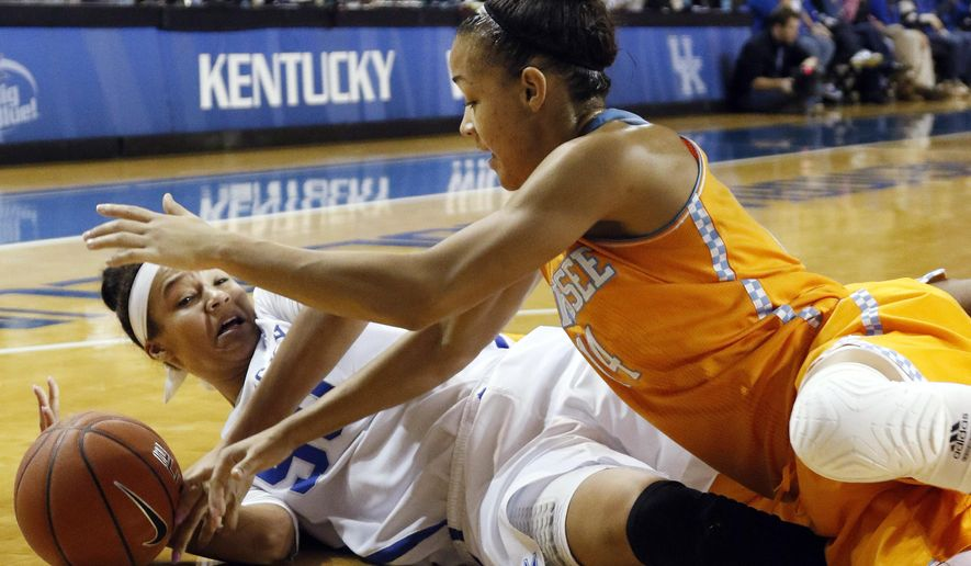 Kentucky's Azia Bishop, left, and Tennessee's Andraya Carter, right, battle for a loose ball during the first half of an NCAA college basketball game in Lexington, Ky., Thursday, Jan. 29, 2015. (AP Photo/James Crisp)