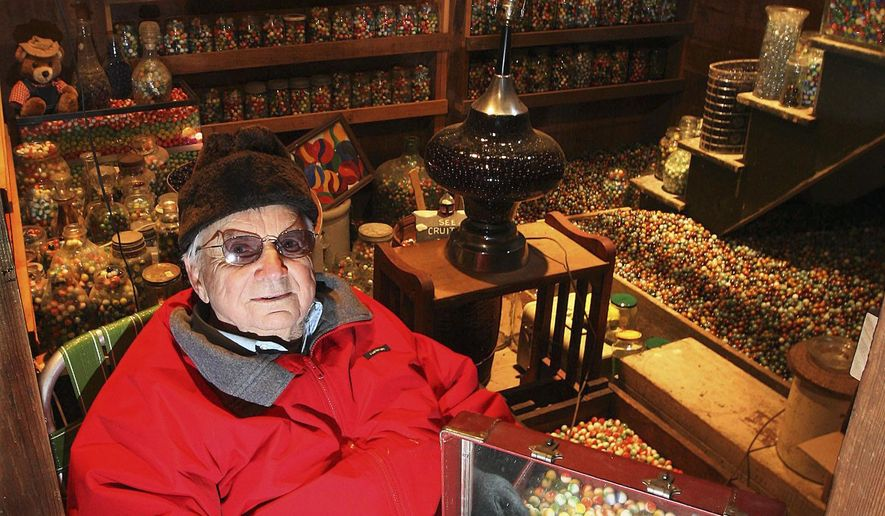 ADVANCE FOR USE SATURDAY, JAN. 31 AND THEREAFTER - In this Dec. 17, 2014 photo, Wayne Cruitt, 87, of Findlay, Ill., sits at home with his collection marbles that has been guessed to be from 500,000 to 1 million. Cruitt began the hobby in the 1930s. (AP Photo/Herald & Review, Jim Bowling)