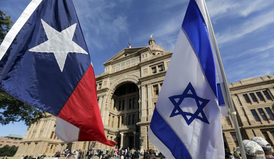 The Texas and Israeli flags are waved by protesters who gathered to disrupt and heckle a group gathered for a Texas Muslim Capitol Day rally, Thursday, Jan. 29, 2015, in Austin, Texas. Hundreds of Muslims gathered for the rally as part of their biennial Texas Capitol lobbying day. (AP Photo/Eric Gay)
