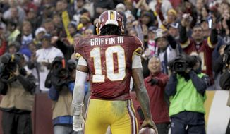 Washington Redskins quarterback Robert Griffin III (10) looks back at the crowd after scoring a touchdown on a keeper during the second half of an NFL football game against the Dallas Cowboys in Landover, Md., Sunday, Dec. 28, 2014. (AP Photo/Mark Tenally)