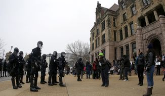 Police officers in riot gear stand across from protesters outside of the St. Louis city hall on Wednesday, Nov. 26, 2014, in St. Louis. Missouri's governor ordered hundreds more state militia into Ferguson on Tuesday, after a night of protests and rioting over a grand jury's decision not to indict police officer Darren Wilson in the fatal shooting of Michael Brown, a case that has inflamed racial tensions in the U.S. (Associated Press) **FILE**