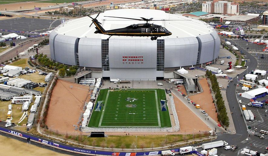 FILE- In this Monday, Jan. 26, 2015, file photo, with the grass field tray outside, a U.S. Customs and Border Protection Black Hawk helicopter circles above University of Phoenix Stadium, site of the NFL Super Bowl XLIX football game, during a security demonstration for the media in Glendale, Ariz.  With a retractable roof and field that can been wheeled out into the sunlight, the stadium is unlike any other stadium in the world. (AP Photo/Ross D. Franklin, File)