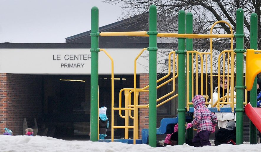 School children play outside a Le Center grade school, Wednesday, Jan. 28, 2015. A proposed city ordinance would prohibit sex offenders from living withint 2,000 feet of places where children gather, including schools, parks and libraries. (AP Photo/Mankato Free Press, John Cross)