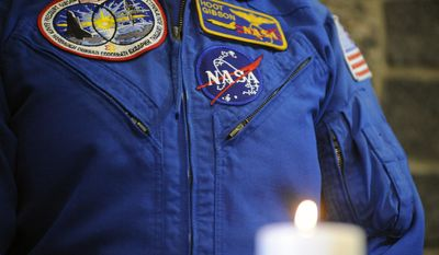 """Five-time shuttle astronaut Robert """"Hoot""""; Gibson stands near a candle honoring fallen astronauts during a remembrance ceremony honoring astronauts killed in three accidents plus 40 others who were part of the astronaut corps and have died, Thursday, Jan. 29, 2015, at Marshall Space Flight Center in Huntsville, Ala.  (AP Photo/Jay Reeves)"""