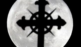 A full moon rises behind a cross on top of Saint Nicholas Catholic Church in the Heights neighborhood of Jersey City, N.J. (Associated Press)