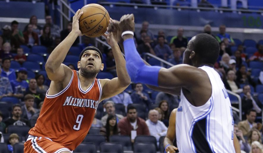Milwaukee Bucks' Jared Dudley (9) goes up for a shot against Orlando Magic's Victor Oladipo, right, during the first half of an NBA basketball game, Thursday, Jan. 29, 2015, in Orlando, Fla. (AP Photo/John Raoux)