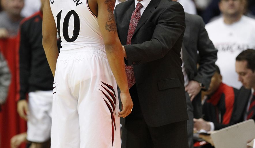 Cincinnati guard Troy Caupain (10) talks to associate head coach Larry Davis after receiving his second technical foul against UConn in the second half of an NCAA college basketball game, Thursday, Jan. 29, 2015, in Cincinnati. Cincinnati won 70-58. (AP Photo/Frank Victores)