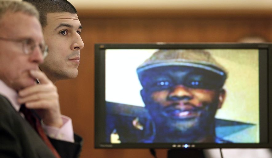 Former New England Patriots football player Aaron Hernandez, center, listens during his murder trial, Thursday, Jan. 29, 2015, in Fall River, Mass., as defense attorney Charles Rankin, left, looks on while an image of Odin Lloyd is displayed on a monitor, right. Hernandez is charged with killing Lloyd, 27, a semiprofessional football player, in June 2013.  (AP Photo/Steven Senne, Pool)