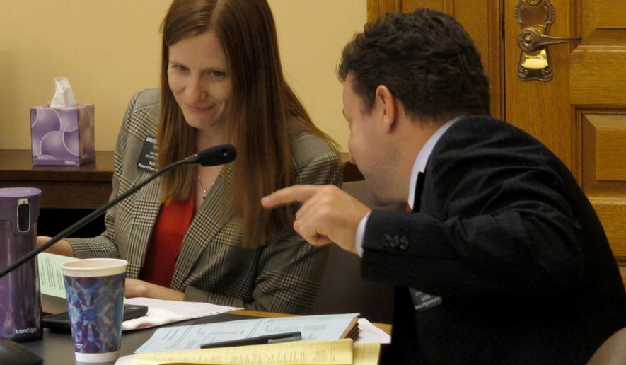 Kansas state Rep. J.R. Claeys, right, a Salina Republican, confers with Rep. Amanda Grosseroad, left, a Lenexa Republican, during a House Appropriations Committee discussion of budget legislation, Thursday, Jan. 29, 2015, at the Statehouse in Topeka, Kan. The committee is working on a bill to balance the current state budget. (AP Photo/John Hanna)