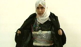 This Nov. 13, 2005, file photo made from television shows Iraqi Sajida al-Rishawi opening her jacket and showing an explosive belt as she confesses on Jordanian state-run television to her failed bid to set off an explosives belt  inside one of the three Amman hotels targeted by al Qaeda. (AP Photo/Jordanian TV, File)  ** FILE **