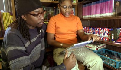 In this 2004 photo Edwin Bradley listens to his daughter, Antoinette, a then-5th-grader, read in the library at South Street School in Newark, N.J. (AP Photo/Mike Derer)