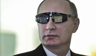 """Russian President Vladimir Putin wears special glasses as he visits a research facility of the St. Petersburg State University in St. Petersburg, Russia, on Monday, Jan. 26, 2015. In televised comments after a meeting with students in St. Petersburg, President Vladimir Putin said that Ukraine's army was at fault for the increase in violence and accused it of using civilians as """"cannon fodder"""" in the conflict. """"(Ukraine's army) is not even an army, it's a foreign legion, in this case a foreign NATO legion,"""" Putin said. """"They have totally different goals, connected to the geopolitical containment of Russia, which absolutely do not coincide with the national interests of the Ukrainian people."""" (AP Photo/RIA Novosti Kremlin, Mikhail Klimentyev, Presidential Press Service)"""