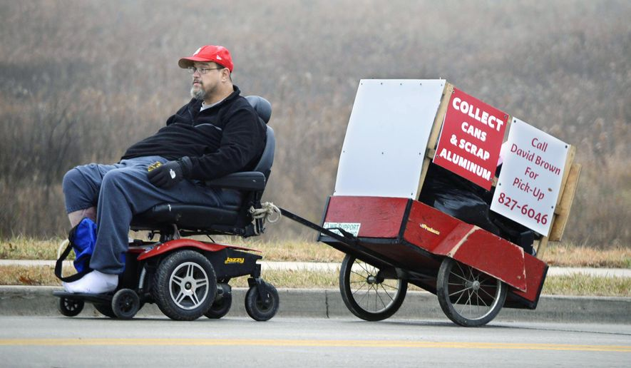 In this Dec. 12, 2014 photo, David Brown, 53, a full-time resident of Asta Care in Bloomington, Ill., departs the center on his electric wheelchair hauling a home made trailer he uses for collecting aluminum cans for recycling. Brown is disabled after breaking his neck after a fall at a job site in Florida in 2008. (AP Photo/The Pantagraph, Steve Smedley)