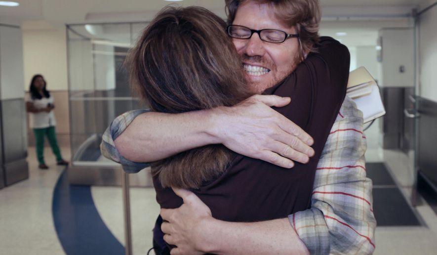"In this Nov. 10, 2013 photo, colleague Luisa Yanez, left, gives Jim Wyss, a welcome hug upon his arrival at the Miami International Airport in Miami. A short-lived promo posted to Twitter by Venezuelan tourism officials to highlight the nation's openness to foreigners featured Wyss who had been detained while covering the country's elections. Earlier this week, the promo ran on the Twitter feed of the state-run Telesur television with a tag-line that read, translated from Spanish, ""We love Venezuela for receiving foreigners like one of our own."" (AP Photo/The Miami Herald, Carl Juste)"
