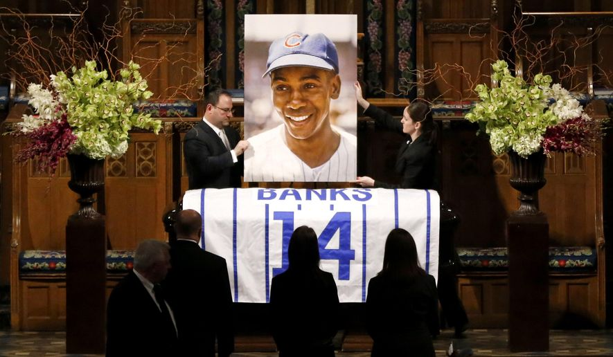 "A large photograph is placed behind the casket of Chicago Cubs Hall of Famer Ernie Banks, during a public visitation held for Banks who died after a heart attack last week, Friday, Jan. 30, 2015, in Chicago. ""Mr. Cub"" is remembered as much for his boundless enthusiasm despite playing on mostly losing teams as his 512 home runs and two MVP awards. A memorial service is scheduled for Saturday on what would have been his 84th birthday. (AP Photo/Charles Rex Arbogast)"