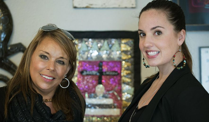 In this photo taken on Thursday, Jan. 15, 2015, Stephanie Reynolds, right, and her mother and business partner, Anne Jordan Reynolds, stand in the Montgomery, Ala., office of their business De La Sol. The Reynolds created De La Sol, a business that is the first and only exporter of Haitian cocoa. They workwith more than 650 cocoa and vanilla farmers and in 2013 opened the first cocoa processing facilities in northern Haiti, employing eight men and women who process the cocoa beans into cocoa butter and cocoa powder.   (AP Photo/Montgomery Advertiser, Albert Cesare) NO SALES