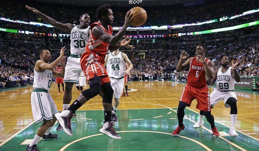 Houston Rockets guard Patrick Beverley (2) looks to pass as he is pressured by Boston Celtics forward Brandon Bass (30) during the second quarter of an NBA basketball game in Boston, Friday Jan. 30, 2015. (AP Photo/Charles Krupa)