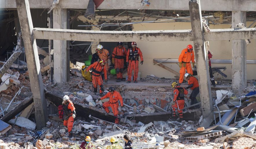 Rescue workers climb out of the wreckage of a maternity and children's hospital amid one of several temporary evacuations as firefighters monitor the leaking gas tanker that caused the explosion in Cuajimalpa on the outskirts of Mexico City, Thursday, Jan. 29, 2015. The explosion, which collapsed the majority of the building, occurred in the morning when a tanker truck was making a routine delivery of gas to the hospital kitchen and gas started to leak. (AP Photo/Rebecca Blackwell)