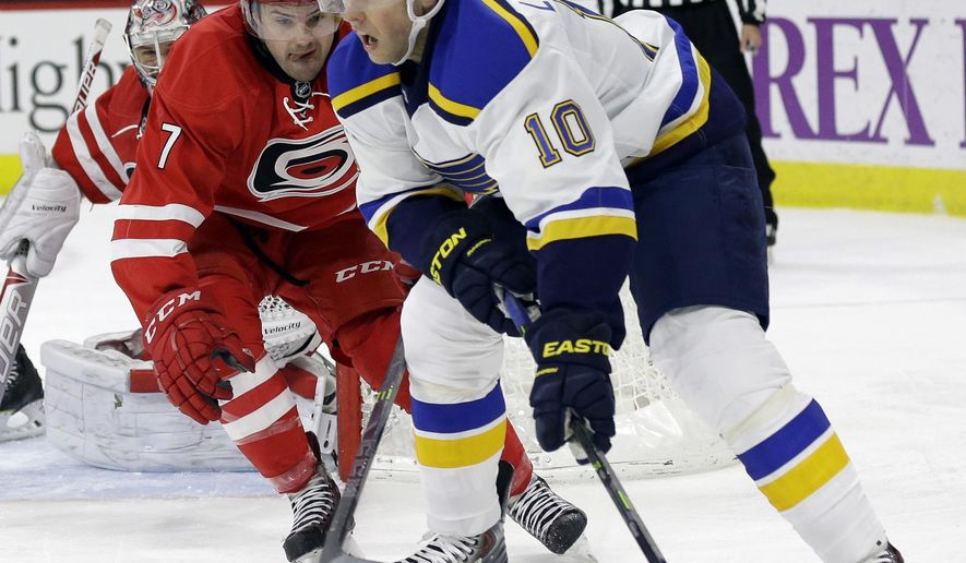 Carolina Hurricanes goalie Cam Ward, rear, and teammate Ryan Murphy (7) defend the goal against St. Louis Blues' Joakim Lindstrom (10), of Sweden, during the first period of an NHL hockey game in Raleigh, N.C., Friday, Jan. 30, 2015. (AP Photo/Gerry Broome)