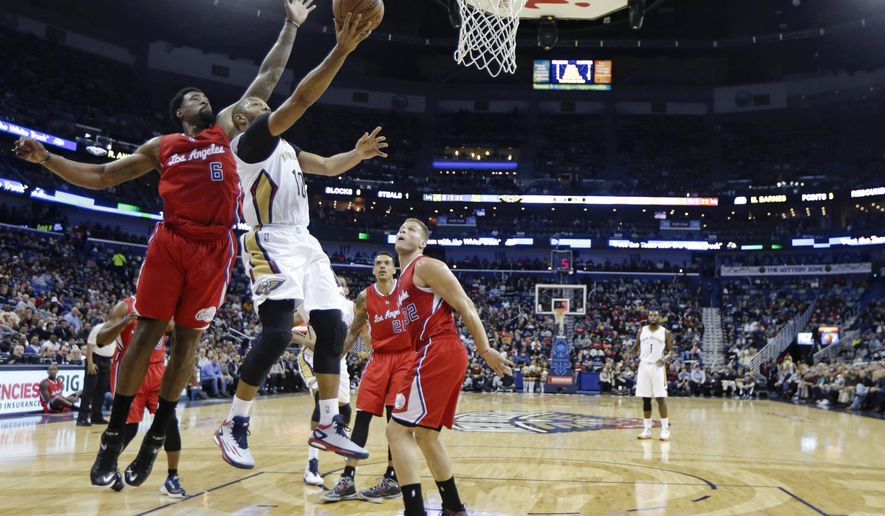New Orleans Pelicans guard Eric Gordon (10) drives to the basket in front of Los Angeles Clippers center DeAndre Jordan (6) during the first half of an NBA basketball game in New Orleans, Friday, Jan. 30, 2015. (AP Photo/Gerald Herbert)