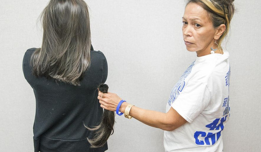 In this photo taken Wednesday, Jan. 28, 2015, Arlette Fontes holds a ponytail of her daughter, Carla Fontes' hair, that was cut off by Carla's wresting coach Stan Haraguchi during a practice at Waiakea High School in Hilo, Hawaii. A friendly bet between a high school coach and a wrestler has led to a suspension and a police investigation in Hawaii. Carla Fontes hadn't cut her hair since intermediate school, but her coach at Waiakea High School, Stan Haraguchi, thought the locks flowing below her waist were interfering with the sport. They bet if she lost a match, he would cut her hair. After a 3-0 start, Fontes lost her first match last week. (AP Photo/Hawaii Tribune-Herald, Hollyn Johnson)   TV OUT
