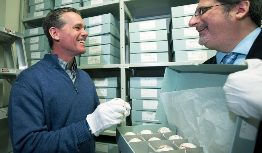 Former Houston Astros player Craig Biggio, left, looks at Yogi Berra autographed baseballs with Erik Strohl, vice president of exhibitions and collections, during his orientation visit at the Baseball Hall of Fame on Friday, Jan. 30, 2015, in Cooperstown, N.Y. Biggio will be inducted to the Hall in July. (AP Photo/Mike Groll)