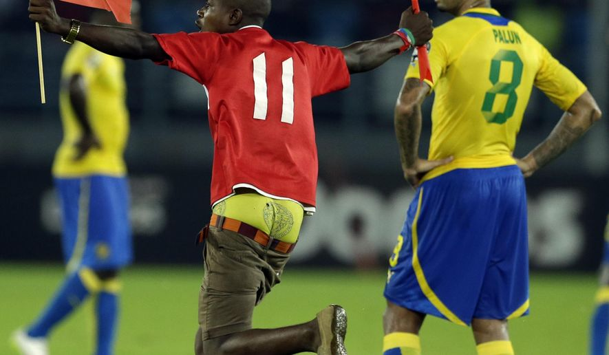 A man holding Equatorial Guinea's national flag runs past Gabon's Lloyd Palun, right, during their African Cup of Nations Group A soccer match in Bata, Equatorial Guinea, Sunday, Jan. 25, 2015. (AP Photo/Themba Hadebe)