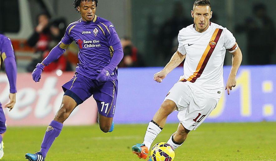 Roma forward Francesco Totti, right,  dribbles past Fiorentina midfielder Juan Cuadrado during a serie A soccer match between Fiorentina and Roma in Florence, Italy, Sunday, Jan. 25, 2015. (AP Photo Fabio Muzzi )