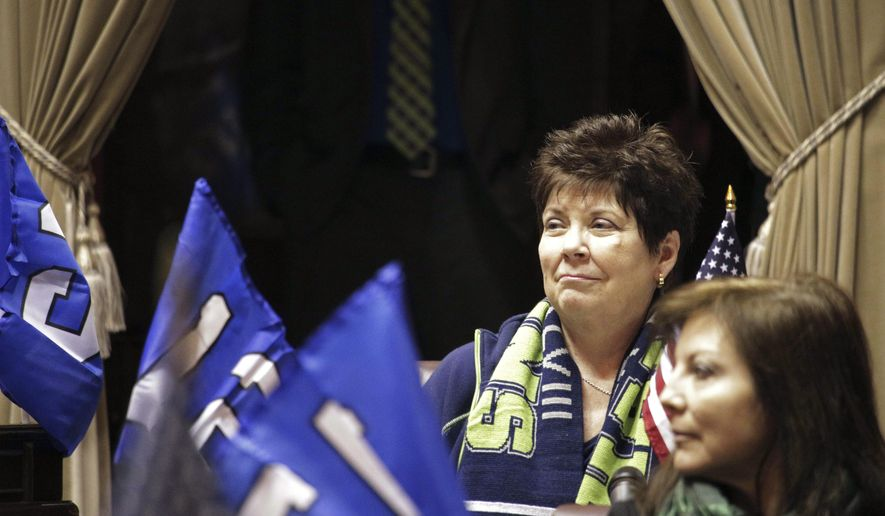 State Republican Sen. Pam Roach, back left, listens to a resolution on the Senate floor honoring the Seattle Seahawks, Friday, Jan. 30, 2015, in Olympia, Wash. Roach is sponsoring a bill that would legalize paid fantasy sports leagues. (AP Photo/Rachel La Corte)