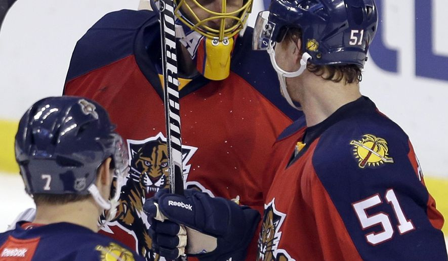 Florida Panthers goalie Roberto Luongo, center, is congratulated by teammates Brian Campbell (51) and Dmitry Kulikov (7) after a 3-2 win against the Columbus Blue Jackets of an NHL hockey game in Sunrise, Fla., Thursday, Jan. 29, 2015. (AP Photo/Alan Diaz)