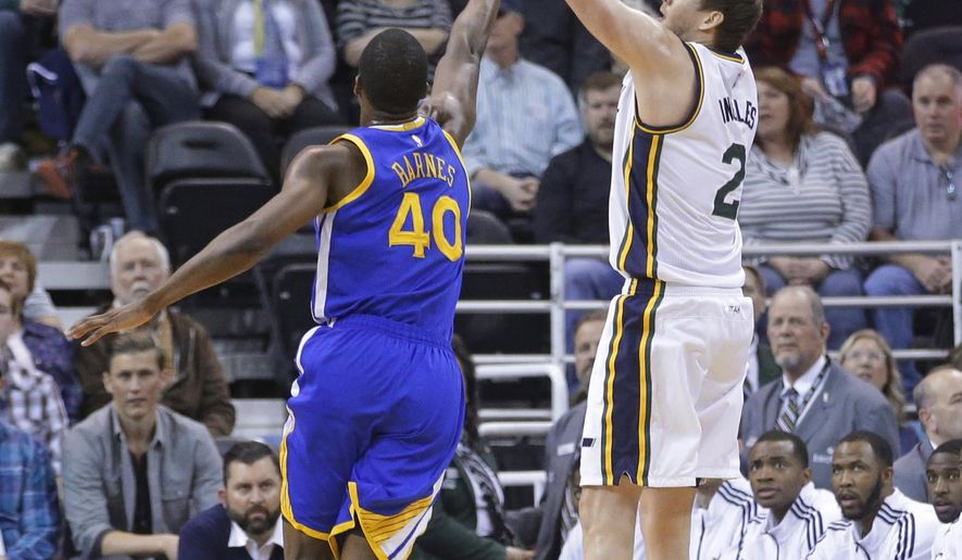 Utah Jazz forward Joe Ingles (2) shoots as Golden State Warriors forward Harrison Barnes defends during the first quarter of an NBA basketball game Friday, Jan. 30, 2015, in Salt Lake City. (AP Photo/Rick Bowmer)