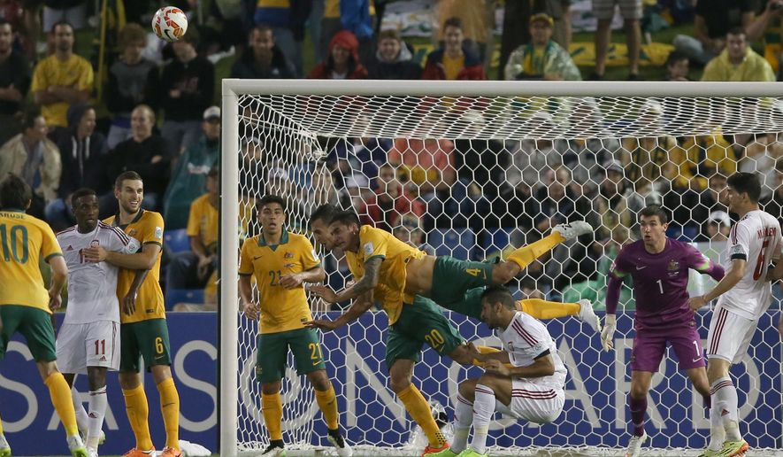 Australia's Tim Cahill, center, and Trent Sainsbury, battle for the ball with UAE's Ali Ahmed Mabkhout, bottom, during the AFC Asian Cup semifinal soccer match between Australia and United Arab Emirates in Newcastle, Australia, Tuesday, Jan. 27, 2015. (AP Photo/Rick Rycroft)