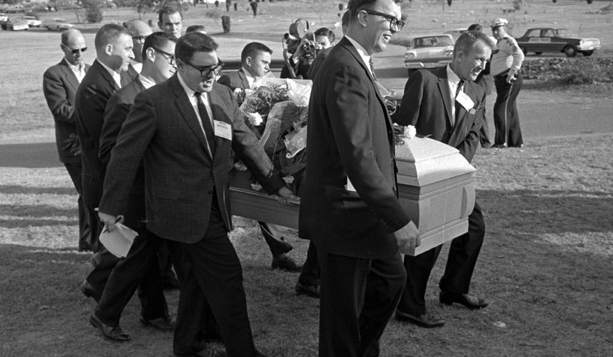 "This file photo shows reporters that were enlisted to act as pall bearers at the interment of Lee Harvey Oswald at the Shannon Rose Hill Cemetery in Fort Worth, Texas. A Tarrant County judge on Friday, Jan. 30, 2015, said the original casket in which Lee Harvey Oswald was buried belongs to Oswald's brother, not the funeral home that auctioned it off for more than $87,000. The judge ordered the funeral home to pay the same amount of money in damages to Robert Oswald, saying its conduct was ""malicious and wanton."" Pallbearers from left end - Jerry Flemmons with crewcut and no glasses. In front of Flemmons are reporters Ed Horn and Mike Cochran. Funeral director Paul J. Groody was among the pallbearers. On the far side of the casket are Jon McConal, rear, and Preston McGraw, front. The pallbearer obscured behind Groody could not be identified. (AP Photo/Gene Gordon, File)"