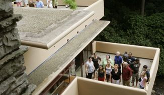 Visitors to Fallingwater, one of the architect Frank Lloyd Wright's best-known works, listen to tour guides as they stand on the concrete terraces in Big Run, Pa., on Aug. 23, 2007. (Associated Press) **FILE**