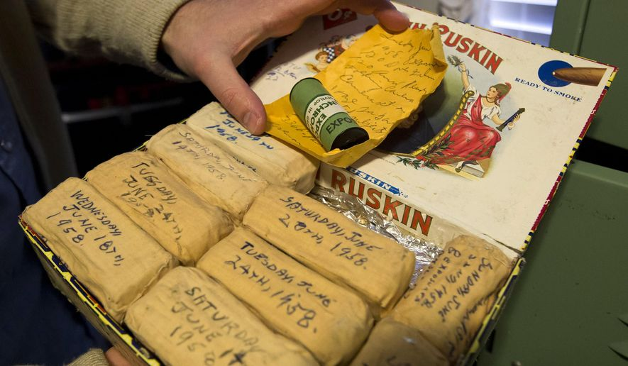 Levi Bettweiser opens a cigar box full of undeveloped rolls of film, meticulously wrapped and sealed from the late 1950's. (AP Photo/The Idaho Statesman, Darin Oswald)