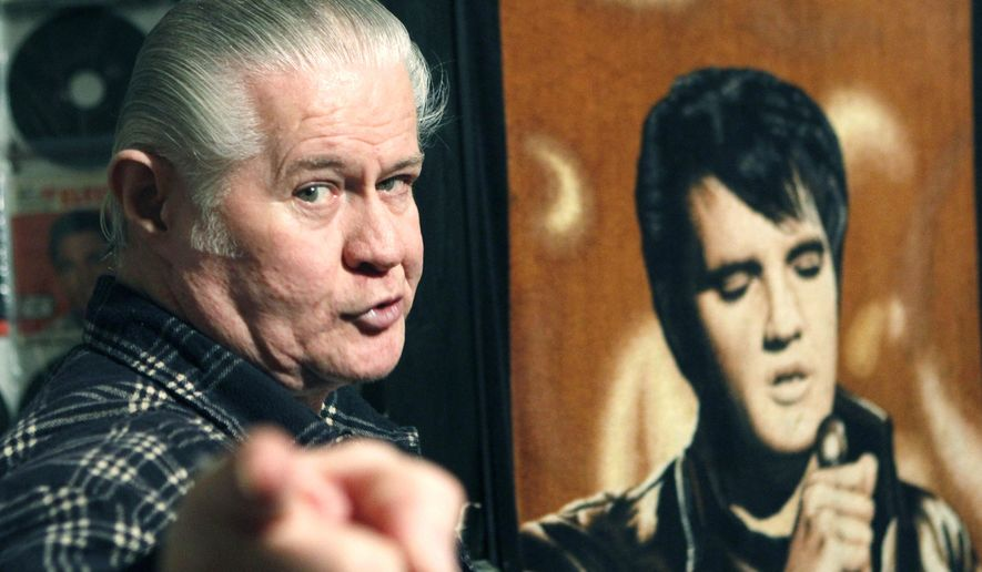 "FILE - This Dec. 9, 2009 file photograph shows the late Paul MacLeod, an Elvis fanatic at the antebellum home he calls ""Graceland Too,"" in Holly Springs, Miss., near a blanket bearing a portrait of his idol. He died July 17, 2014. MacLeod's two-story home and its Elvis-centric contents are to be auctioned Saturday, Jan. 31, 2015. (AP Photo/Rogelio V. Solis)"