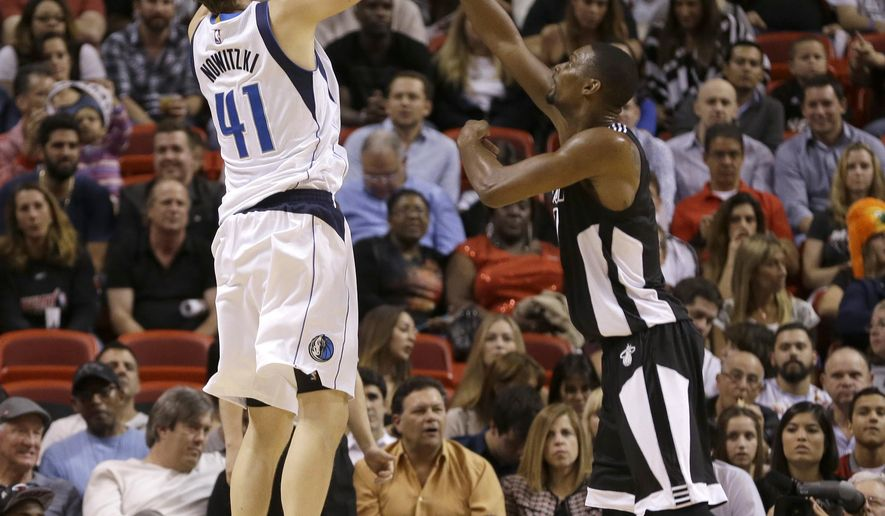 Dallas Mavericks forward Dirk Nowitzki (41) prepares to shoot against Miami Heat center Chris Bosh (1) in the first of an NBA basketball  game in Miami, Friday, Jan. 30, 2015. (AP Photo/Alan Diaz)