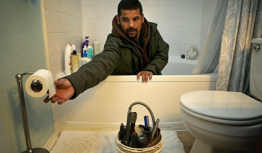 In this photo taken on Thursday, Jan. 15, 2015, Anthony Cartagena, who is a plumber with Parker & Sons Plumbing, works cleaning out a bath tub drain in a client's home, in San Antonio, Texas.  A master plumber, Cartagena learned the craft from his father-in-law, instead of following his own father into a life of street crime.  (AP Photo/The San Antonio Express-News, Bob Owen )  RUMBO DE SAN ANTONIO OUT; NO SALES