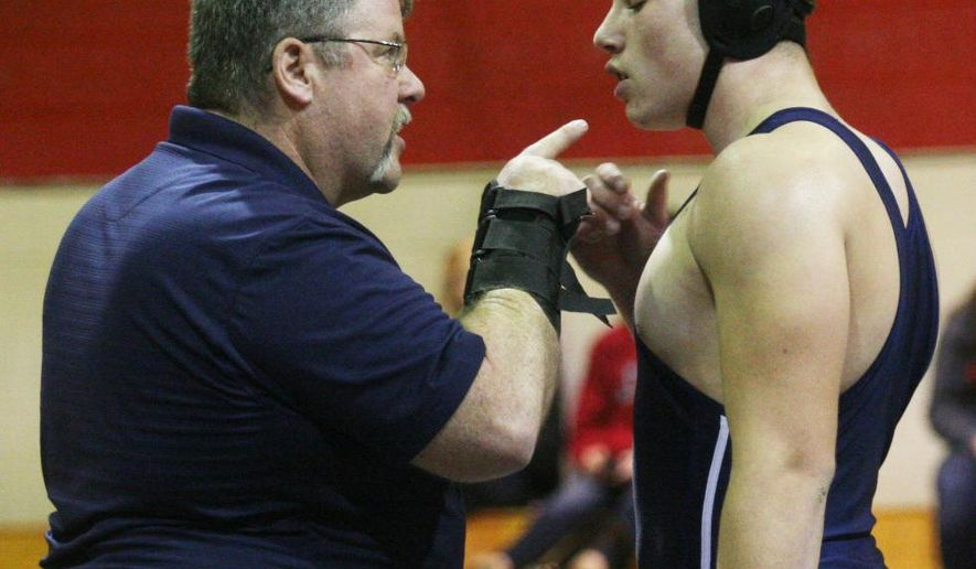 ADVANCE FOR WEEKEND EDITIONS SUNDAY FEB. 1 - In this Dec. 17, 2014 photo, Northside wrestling coach Dave Pelsang, left, gives instructions to wrestler Sam Barbosa during a wrestling match in Jacksonville, N.C. When Dave Pelsang received the email from USA Wrestling informing him he'd been selected as one of the officials for an international tournament in Cuba, Northside's first-year coach wasn't sure what to think.(AP Photo/The Jacksonville Daily News, Rick Scoppe)
