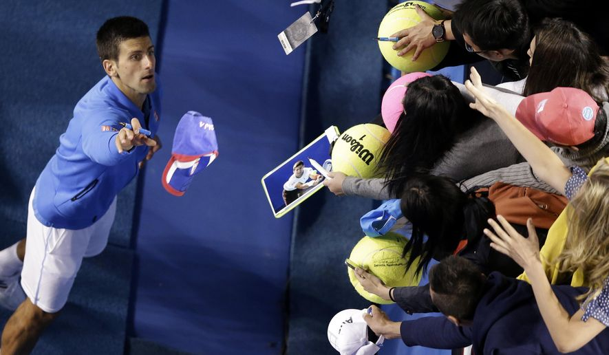 Novak Djokovic of Serbia throws a cap to the spectators after defeating Milos Raonic of Canada in their quarterfinal match at the Australian Open tennis championship in Melbourne, Australia, Wednesday, Jan. 28, 2015. (AP Photo/Lee Jin-man)