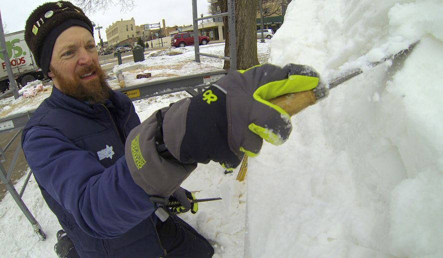 In this photo taken Jan. 29, 2015 in Lake Gevena, Wis., sculptor David Andrews, of one of the Wisconsin teams,  carves a nine-foot high block of snow during the U.S. National Snow Sculpting Championship. He and his various teams have won seven national championships. (AP Photo/Carrie Antlfinger)