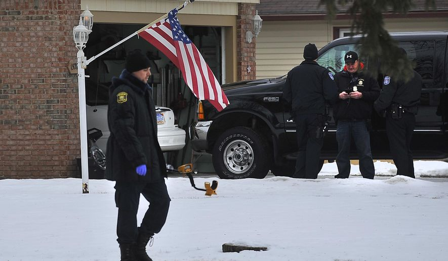 Police technicians collect evidence at the scene of a homicide, in Southgate  Mich., on Thursday, Jan. 29, 2015.  Authorities say a 74-year-old Southgate man fatally shot an armed neighbor who broke into his home. Police officials say the neighbor entered the home through a window early Thursday morning while the couple who lives there was sleeping.  According to police, the neighbor pointed his gun at the 74-year-old, prompting him to fire a shot.  (AP Photo/Detroit News, Daniel Mears)  DETROIT FREE PRESS OUT; HUFFINGTON POST OUT