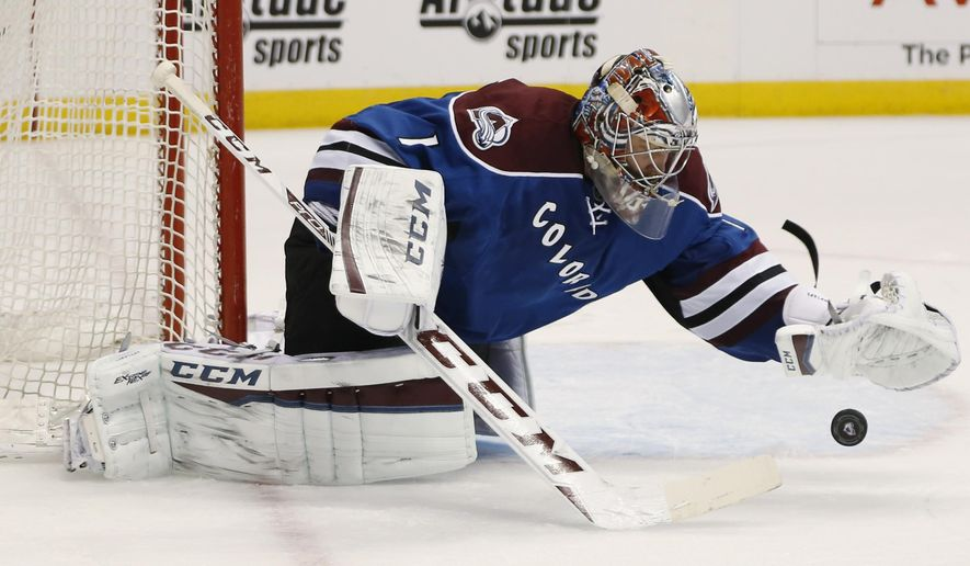 Colorado Avalanche goalie Semyon Varlamov, of Russia, uses his glove to cover the puck as he falls to the ice after stopping a shot against the Nashville Predators in the second period of an NHL hockey game Friday, Jan. 30, 2015, in Denver. (AP Photo/David Zalubowski)