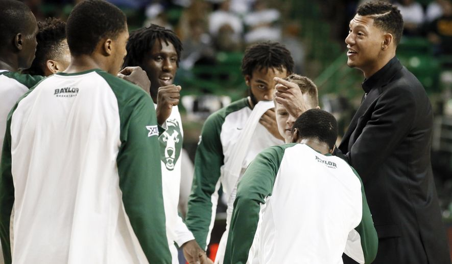 ADVANCE FOR WEEKEND EDITION, JAN. 31-FEB. 1 - In this photo taken Jan. 14, 2015, Baylor student assistant Isaiah Austin, right, talks to the team before an NCAA college basketball game against Iowa State in Waco, Texas. These are not exactly the big basketball dreams once imagined by the 7-foot-1 Austin, the player with a prosthetic eye who only days before the draft last year was diagnosed with a rare genetic disorder that can affect his heart. He now works to make people aware of Marfan Syndrome, with a positive attitude he hopes will help others overcome their obstacles.  (AP Photo/Tony Gutierrez)